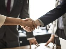 Agent immobilier qui sert la main de son client après la signature d'un acte de vente